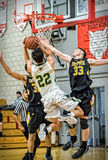 Splitting the Defense. A Placer player (white) goes up and shoots between two Enterprise players l in Redding, California. December 5, 2015 royalty free stock images