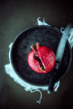 Splitting open a pomegranate with a knife Royalty Free Stock Images