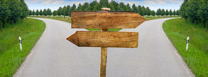 Splitting road blank crossroad wooden blabk signs Royalty Free Stock Photo