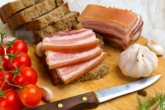 Splitting salty bacon with cherry tomatoes. Royalty Free Stock Images