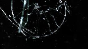 Splittrade och brutna exponeringsglasstycken som isoleras på svart Arkivbild