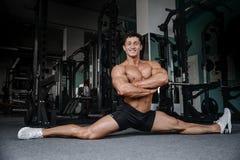 Splittringelasticitetsman som sträcker ben i den stiliga konditionen för idrottshall Arkivfoto
