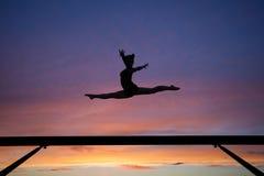 Splittringhoppet på balansbommen i solnedgång Royaltyfri Fotografi