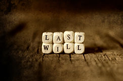Splotchy retro effect on photo concept last will and testament. Small wooden blocks with letters on the old worn wooden table Stock Image