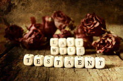 Splotchy retro effect on photo concept last will and testament. Small wooden blocks with letters on the old worn wooden table Stock Images