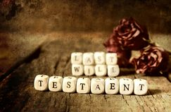 Splotchy retro effect on photo concept last will and testament. Small wooden blocks with letters on them are laid in the floor on the old wooden table Stock Image