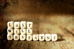 Splotchy retro effect on photo concept last will and testament. Small wooden blocks with letters on them are laid in the floor on the old wooden table Stock Images