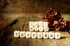 Splotchy retro effect on photo concept last will and testament. Small wooden blocks with letters on them are laid in the floor on the old wooden table Stock Photo