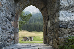Medieval castle door. View through the empty doorway arch of an ancient castle ruin on two huts. Green forest and meadow visible in the background Royalty Free Stock Photography