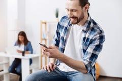 Społecznie aktywny wibrujący facet czyta newsfeed zdjęcia stock