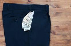 spodnia i dolary w kieszeni na starym drewnianym stole Zdjęcie Stock