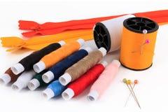 Spoel van draad met naald, spelden, draad van de ritssluitingen de kleurrijke naaiende spoel Royalty-vrije Stock Foto's