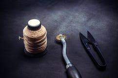 Spoel van gele draden en hulpmiddelen op zwarte achtergrond royalty-vrije stock afbeelding
