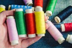 Spoel van groene, rode, roze en gele naaiende draad in een vrouwelijke hand tegen de achtergrond van andere spoelen van draad op  royalty-vrije stock afbeeldingen