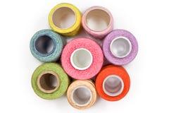 Spoelen met multi-coloured naaiende geïsoleerdeg draden Stock Foto's