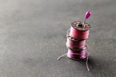 Spoelen met roze draad en een speld op een zwarte achtergrond stock afbeelding