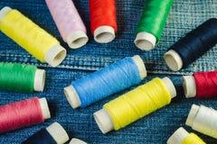 Spoelen van blauwe, witte, roze, rode en groene naaiende draad op blauw denim stock foto