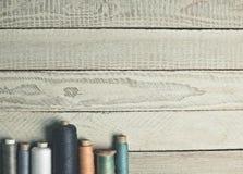 Spoelen van draad op een witte houten oppervlakte Stock Foto