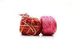 Spoelen van roze en bruine die draad en naald op witte achtergrond wordt geïsoleerd Stock Fotografie