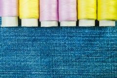 Spoelen van roze en gele naaiende draad op blauw denim met exemplaarruimte royalty-vrije stock fotografie