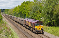 Spoil train. BEACONSFIELD, UK - MAY 15: An EWS operated spoil freight takes a train of empty wagons into London to pick up Crossrail spoil. EWS now owned by DB Royalty Free Stock Photo