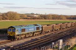 Spoil train in rural setting. HARROWDEN, UK - MARCH 7: A Freightliner operated class 66 diesel locomotive hauls a rake of spoil wagons towards the open cast site Stock Photography