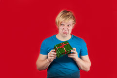 Spoiled. Young man holding gift on red background Stock Images
