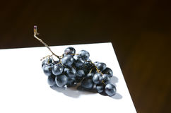 Spoiled grapes on table. Blue spoiled grapes on a white board Royalty Free Stock Image