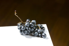Spoiled grapes on table. Blue spoiled grapes on a white board Royalty Free Stock Photo
