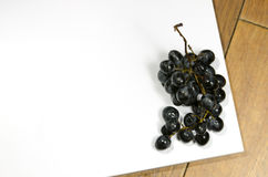 Spoiled grapes on table. Dark spoiled grapes on a white board Royalty Free Stock Photos