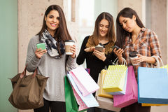 Spoiled housewives at a shopping center. Group of young and spoiled housewives hanging out at a shopping mall and holding bags, coffee and smartphones Royalty Free Stock Photos