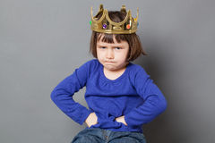 Spoiled kid concept illustrated with a crown. Spoiled kid concept - sulking preschool child with golden crown on head putting hands on hips for confident Stock Image