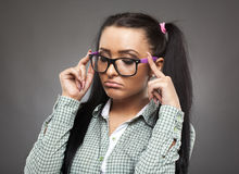 Spoiled nerd brat. Sulky girl with nerd glasses and pigtails posing as a spoiled brat on gray background Stock Photos