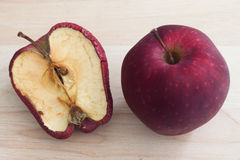 Spoiled one bad red apple on wooden background Healthy and rotte Royalty Free Stock Images