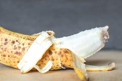 Spoiled peeled banana. On a grey background Stock Photo