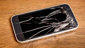 Spoiled phone with beaten glass on a wooden background_. Spoiled phone with beaten glass on a wooden background stock photo