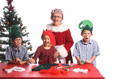 Spoiled Surprise. A group of young children aged 6 - 12 wearing elf hats and working with Mrs. Santa Claus on a Christmas craft project of decorating a stocking Stock Image