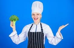 Spojrzenie Fachowy szef kuchni ono uśmiecha się z organicznie brokułami podczas gdy gestykulujący daleko od Szczęśliwy kobiety re zdjęcia stock