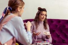 Spokój i pokojowa ciemnowłosa dziewczyna niesie filiżankę herbata i opowiadać zdjęcia royalty free