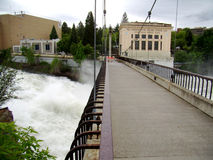 Spokane Floodwater Footbridge. Spokane River rises above flood stage and the parks department closes one of the two Canada Island bridges. Here the water is stock photography