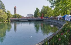 Spokane River in Riverfront Park with Clock Tower. Flowers, people, bridge and vendors Stock Photo