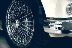 Spoked wheel of a white luxury car. Antique automovile and empty copy space. For Editor`s text Royalty Free Stock Images