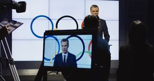 Spokesman holding press conference on stage. Confident representative in formal suit giving speech on press conference for Olympic Games standing on scene in stock video footage