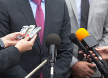 Spokesman. News conference. Media interview. Microphones. Journalists making interview with businessman or politician. Broadcast journalism Royalty Free Stock Photos
