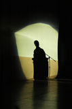The spokesperson`s shadow. Spot light on the spokesperson projects his shadow onto the back curtain Stock Photography