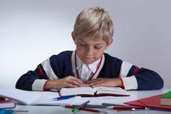 Spokojna chłopiec robi pracie domowej Obrazy Stock