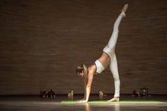 Spokojna dama stawia jeden nogę w górę podczas gdy ćwiczyć nową joga pozę obraz royalty free