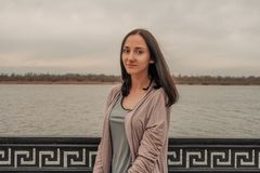 Spokojna dziewczyna stoi samotnie na nabrzeżu przed ogrodzeniem obraz stock