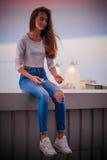 Spokojna dziewczyna w cajgach siedzi w wiatrze zdjęcie stock