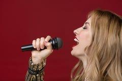 Spokojna kobieta utrzymuje mikrofon w ręce i skandować obrazy royalty free